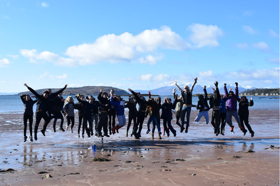 A large group of students on the beach are captured jumping into the air.